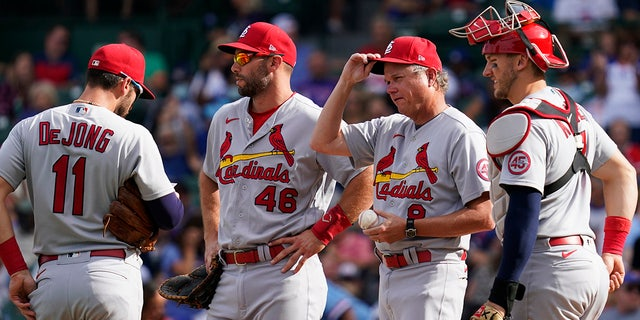 St. Louis Cardinals manager Mike Shildt, second from right, talks with shortstop Paul DeJong, left, first baseman Paul Goldschmidt, second from left, and catcher Andrew Knizner, right, as they wait for relief pitcher Andrew Miller during the sixth inning of a baseball game against the Chicago Cubs in Chicago, Sunday, Sept. 26, 2021.