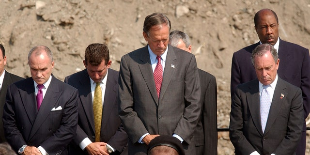 (L TO R) New York Police Commissioner Raymond Kelly, New York Governor George Pataki and New York Mayor Michael Bloomberg bow their heads at a memorial service for those killed during the September 11 attacks at the World Trade Center July 15, 2002, at Fresh Kills Landfill in the New York City borough of Staten Island. (Photo by Spencer Platt/Getty Images)