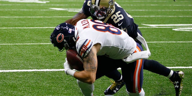 Chicago Bears tight end Zach Miller (86) injures his leg as pulls in a touchdown reception that was ruled incomplete upon review as New Orleans Saints defensive back Rafael Bush (25) covers in the second half of an NFL football game in New Orleans, Sunday, Oct. 29, 2017. (AP Photo/Butch Dill)