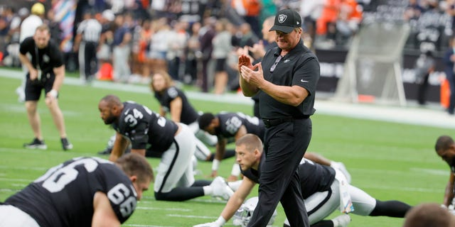 Head coach Jon Gruden of the Las Vegas Raiders talks to his players as they stretch before a game against the Chicago Bears at Allegiant Stadium Oct. 10, 2021 in Las Vegas, Nev.