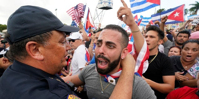 In this Wednesday, July 14, 2021, file photo, Miami Police Chief Art Acevedo, left, hugs a demonstrator, in Miami's Little Havana neighborhood, as people rallied in support of antigovernment demonstrations in Cuba. City of Miami commissioners held a special meeting last month in which they attacked Acevedo less than six months into his post, and voted to further investigate him and his appointment. (AP Photo/Wilfredo Lee, File)